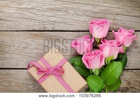 Pink roses and valentines day gift box over wooden table. Top view with copy space