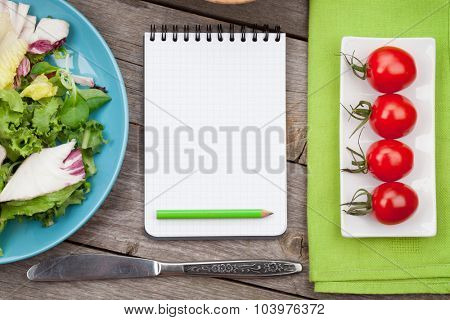 Fresh healthy salad, tomatoes and notepad for copy space on wooden table