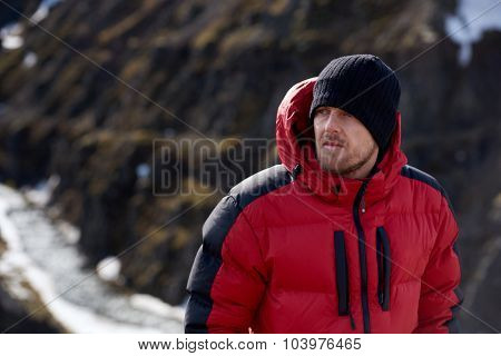 portrait of man in wilderness rugged mountain landscape determined to climb to the summit in red snow gear
