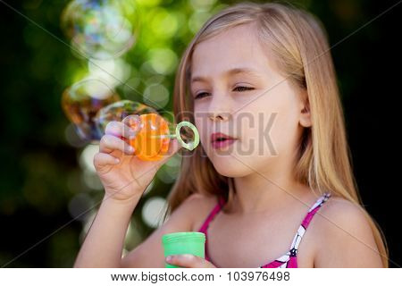 Cute little caucasian girl blowing soap bubbles
