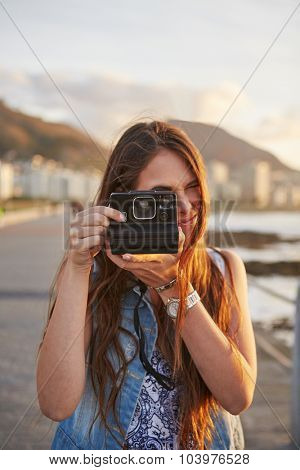 Woman with instant camera taking pictures on vacation summer beach holiday