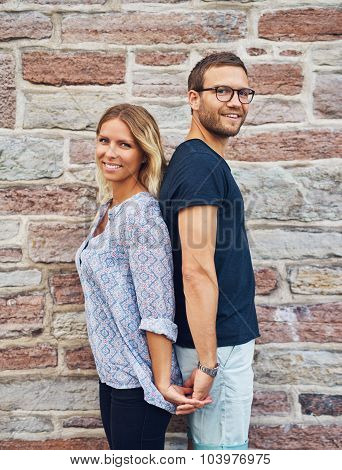 Couple Standing Back To Back And Holding Hands