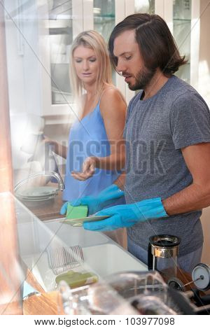 Young caucasian couple doing household chores in kitchen, domestic routine at home