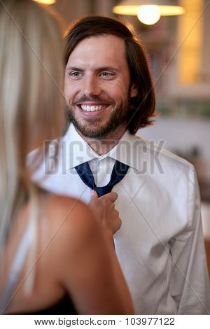 woman helping man with tie early morning for work formal event
