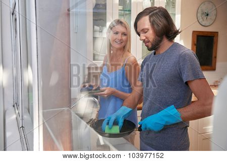 Happy caucasian couple doing household chores in the kitchen