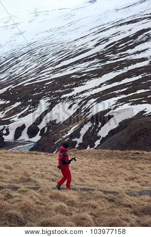 Tourist walking alongside Iceland mountain scape in harsh winter cold conditions