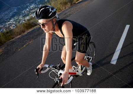 Healthy active female riding bicycle on road for sport training