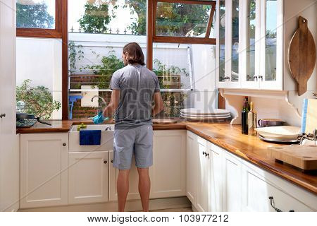 Rear view of male in the kitchen doing household chores