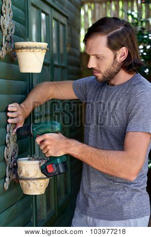young caucasian DIY male mounting potted plants