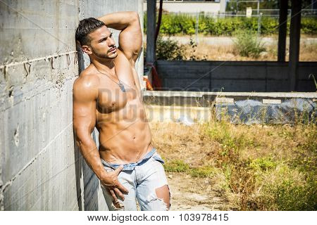 Muscular construction worker shirtless in building site