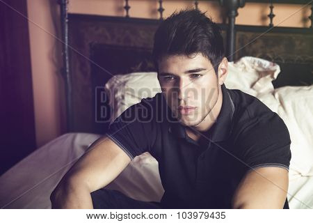 Handsome young man sitting on his bed