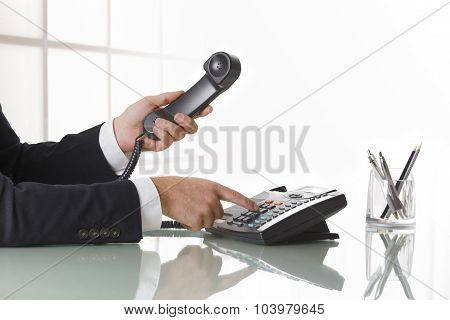Businessman Hands Dialing Out On A Black Deskphone
