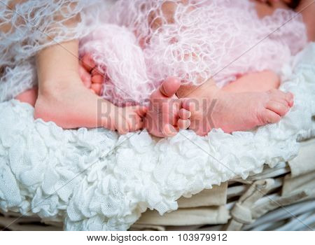 small feet newborn twins wrapped in a blanket
