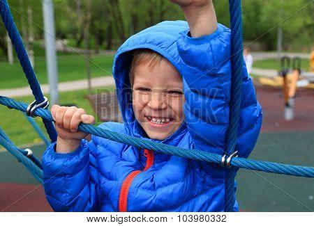 child climbing rope on the playground