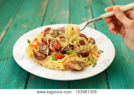 Spaghetti Al Pomodoro In White Plate With Hand Holding A Winding Fork On Wooden Turquoise Table