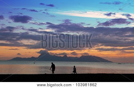 Sunset over the sea and mountains the fisherman's silhouette ashore. Tahiti.