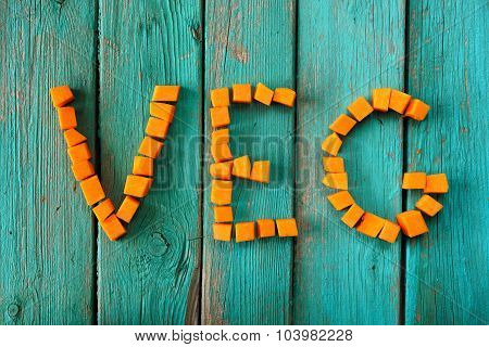 Word Veg Written With Raw Pumpkin Pieces On Wooden Turquoise Table