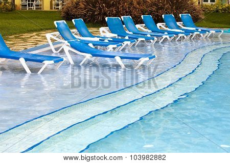 Empty beach chairs near pool in a sunny day