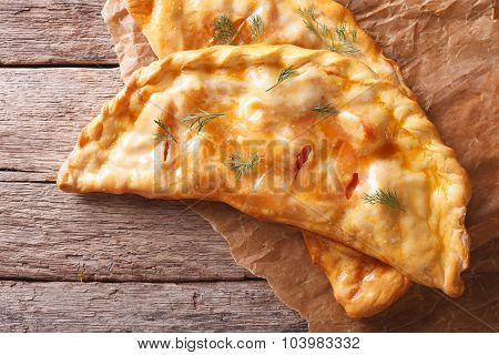 Homemade Calzone Close-up On A Paper. Horizontal Top View