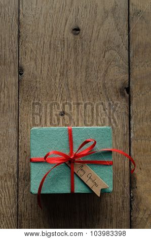 Turquoise Gift Box With Red Ribbon And Vintage Style Christmas Tag