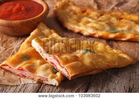 Cut Italian Pizza Calzone With Ham And Cheese Close-up. Horizontal