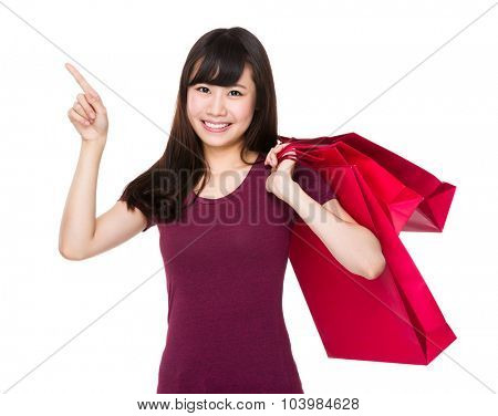 Woman hold with shopping bag and finger point aside