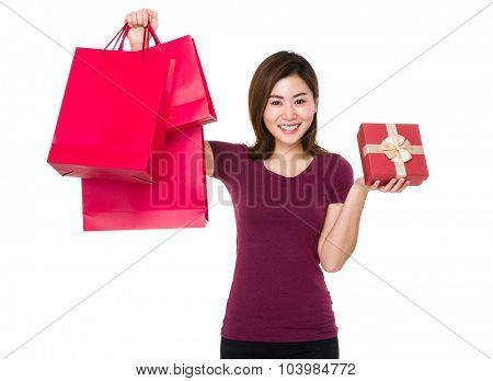 Woman holding up with shopping bag and gift box