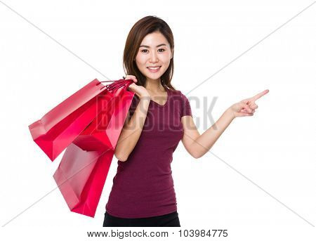 Asian woman holding with shopping bag and finger point up