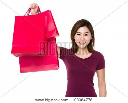Young woman holding up with shopping bag