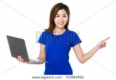 Woman hold with laptop computer and finger point aside