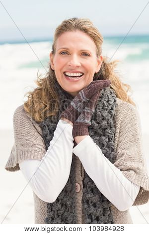 Smiling woman wearing winter clothing at the beach