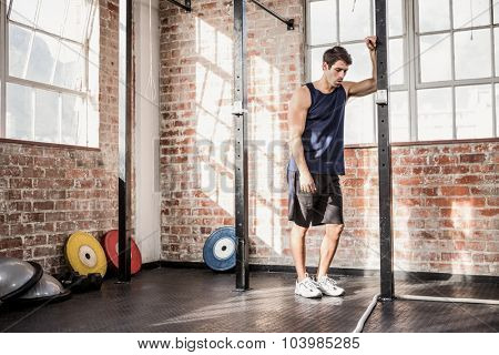 Man leaning on a pole at the gym