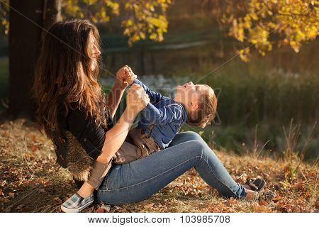 Happy young mother and  son having fun outdoor  autumn day