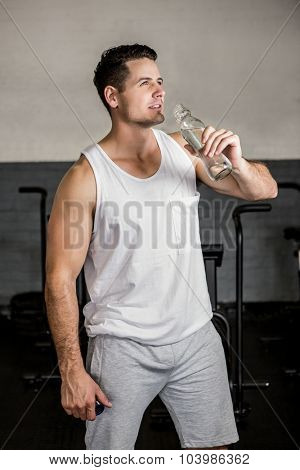 Muscular man holding water bottle at the gym
