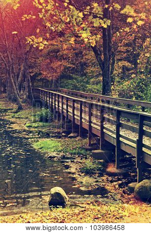 Beautiful wooden bridge during the fall with retro style toning