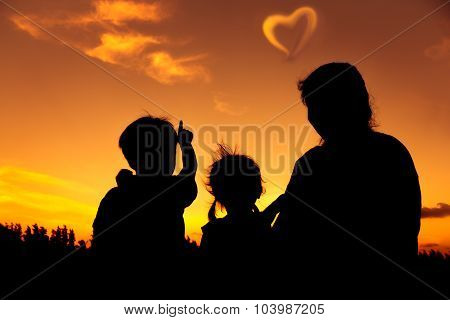 Silhouette Of Happy Family Sitting And Looking Sky At Sunset.