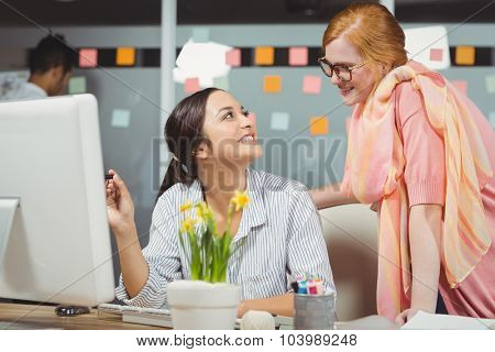 Happy businesswomen using computer in office with male colleague working in background