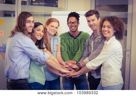 Portrait of smiling business people with hand stacked during meeting in creative office
