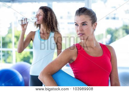 Pretty women in fitness studio holding exercise mat and water bottle