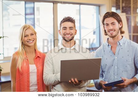 Portrait of happy business people using laptop in creative office