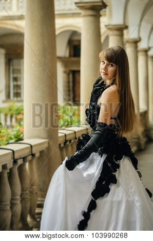 Beautiful Young Woman In White Dress With Black Roses Standing Back
