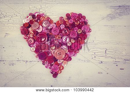 Heart from red buttons on a white wooden background