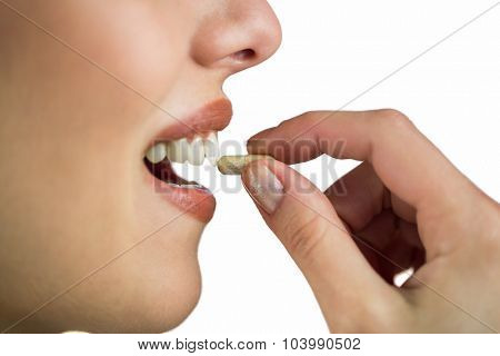 Close-up of woman taking pill on white background
