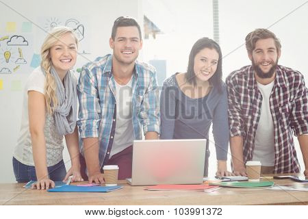 Portrait of smiling business people while standing at desk