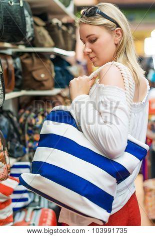 Young Woman Choosing Beach Bag In The Shop.