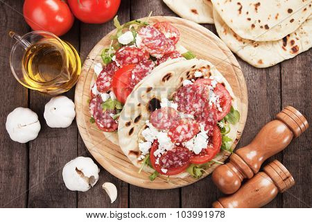 Piadina Romagnola, Italian Flatbread Sandwich with Pepperoni, ricotta cheese, tomato and rocket salad