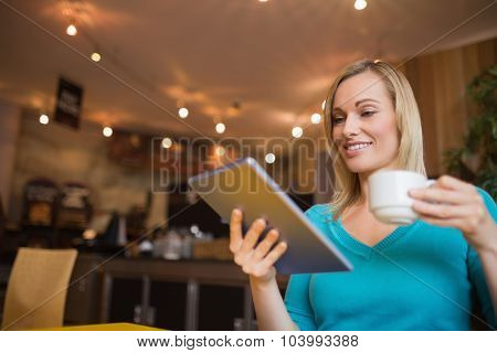 Low angle view of young woman using digital tablet while holding cup in cafe