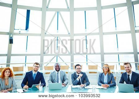 Successful managers sitting in conference hall and looking at camera