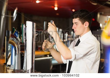 Side view of barkeeper holding glass in front of beer dispenser at bar