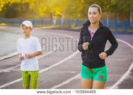 mother and son are running or jogging for sport outdoors